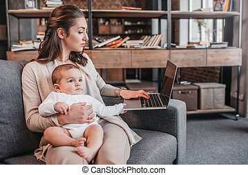 Concentrated mother with her son sitting on couch and using...