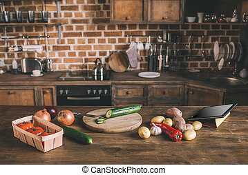 Kitchen table with variety of raw vegetables, chopping board and digital tablet ready for preparing breakfast
