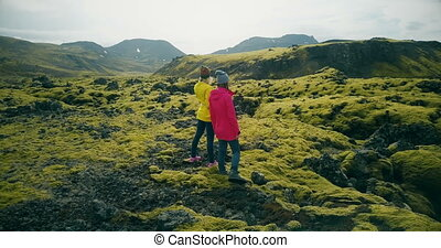 Aerial view of two woman walking on the lava fields in Iceland. Tourists enjoying the landscape, exploring the territory