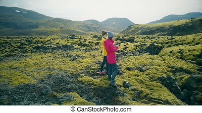 Aerial view of two tourists woman walking on lava fields in...