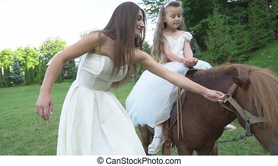 Mother rolls her daughter on a pony - Mom rolls a little...
