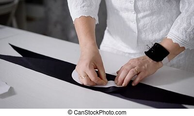 Female tailor making pattern on tissue by pinning paper...