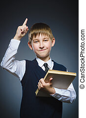 Smiling preteen boy have idea with book holding finger up on...