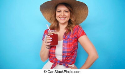 Beautiful young woman drinking strawberry smoothie on blue...