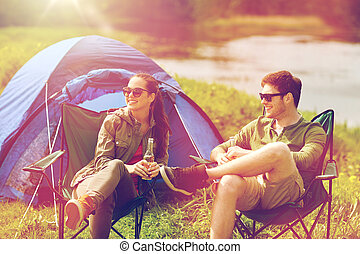 happy couple drinking beer at campsite tent
