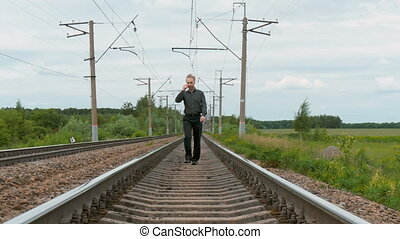 A person in a bad mood walks the railway tracks. Problems,...