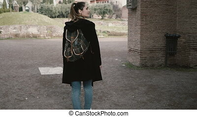 pretty young girl is walking around Rome, Italy, seeing over an antique. The tourist is exploring the ancient ruins.
