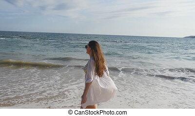 Happy woman in bikini and shirt walking on the beach near...