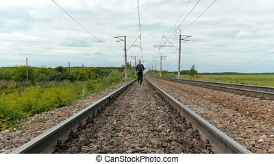 A man with a laptop runs along the railroad tracks.