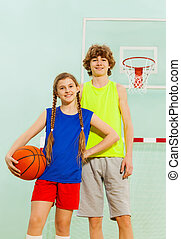 Happy basketball players posing with ball in gym