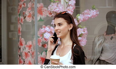 pretty lady keep in her hand a glass of coffee and talking on the phone