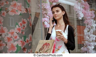 beautiful girl with shopping and a glass of coffee stands near the showcases