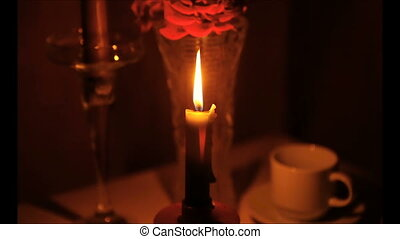 On the table are burning candle. Disconnected electricity.