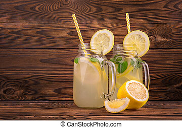 Fresh and tasty drinks with yellow straight straw and lemons, mint, and ice on a wooden table. Refreshing lemonade in glass, pitcher, and citrus fruit around on brown wooden table close-up.