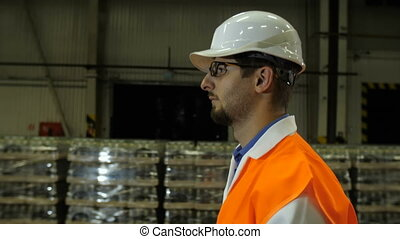 Worker at hard hat moving through the storage - Engineer at...