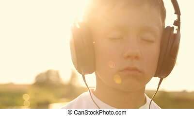 Boy listening to music through headphones in the nature...