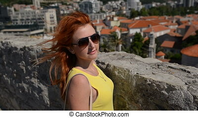 Red-haired woman with flying hair on the background of the old city