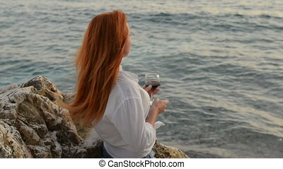 Young woman with flying hair standing with a glass of wine on the rocky beach of the Adriatic Sea