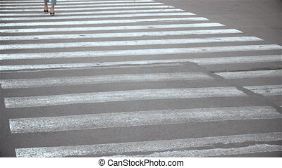 a young girl walks on a pedestrian crossing in close-up