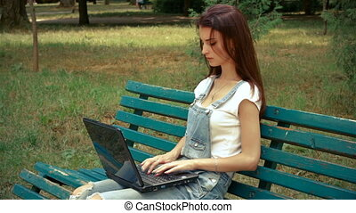 cute brunette sitting on a bench and prints on a laptop