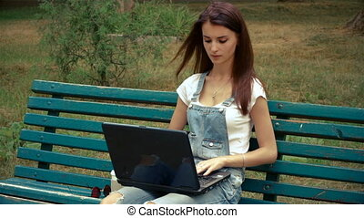 beautiful young girl looking at a laptop while sitting on a bench