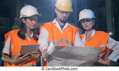 Team of engineers with drawings - team of engineers looking...