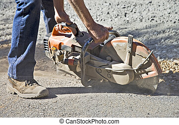 Man Cutting Asphalt - A worker cutting the edge on asphalt...