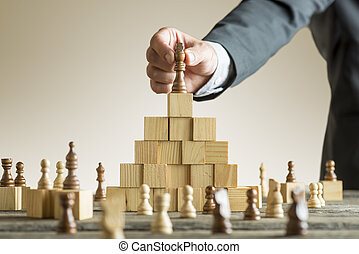 Businessman placing a chess piece on blocks - Businessman...
