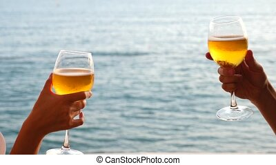 Two people clink glasses with alcohol on the background of the sea. Close-up, slow-motion