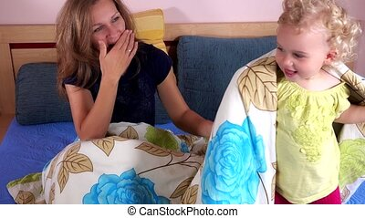 Loving mother have fun with cute daughter girl on bedroom bed