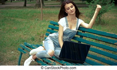 attractive young girl in a park on your laptop and prints...