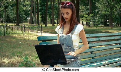 glamorous young girl with glasses sits in the Park opens...