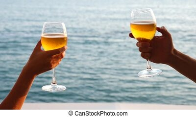 Two people clink glasses with alcohol on the background of...