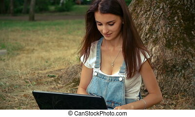 brunette sitting near a tree and looking at laptop -...