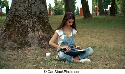 cute girl sitting near a tree in summer and prints on a laptop