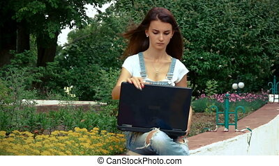 cute girl sitting near a flowerbed and looks at laptop