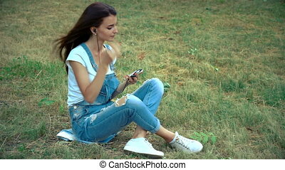 pin-up girl sits on the grass and inserts in-ear headphones...