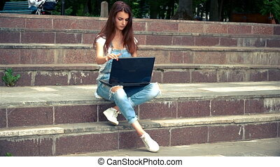 women sitting on the steps in with a laptop - attractive...