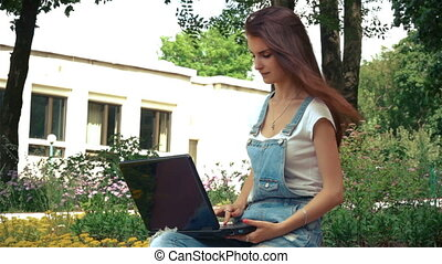 brunette teen sits in the wind on the street with a laptop