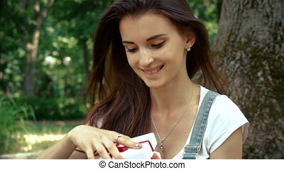 wonderful girl sitting outdoors in the Park and opens a gift...
