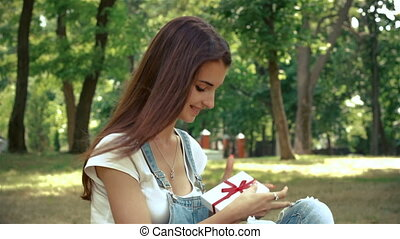 cute brunette sits in the summer in the Park and holds a...