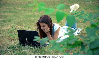 lovely girl looks in laptop and lies in a park on the grass...