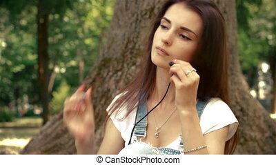 beautiful young lady with headphones in your ears, sitting...