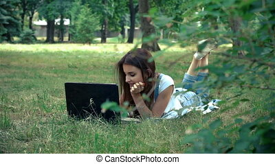 cute brunette lies in the summer on the grass and looking at laptop