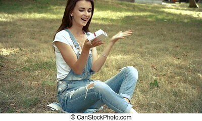 brunette sits on the grass and holding a gift box with a bow