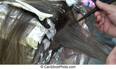 woman at the hairdresser,hair stylist dyes her hair