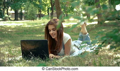 charming lady looks in laptop lying on the green grass -...