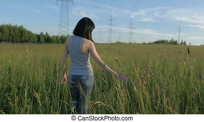 A young woman is walking along the field.
