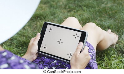 Woman on grass with tablet - Anonymous woman in straw hat...