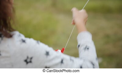 Girl holding a rope with a kite